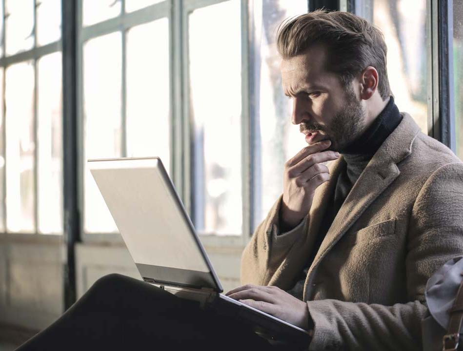 man on a laptop checking his investments
